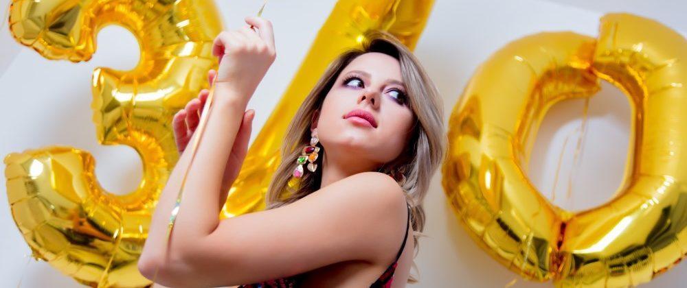Kvinde der står med balonner der viser at hun bliver 30 år